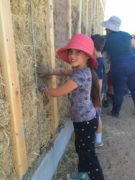 "Third grader on a field trip to the Canelo Project, having a hands-on experience of learning straw bale construction methods as part of the ""Living on the Earth"" focus which includes farming, textiles, and construction."
